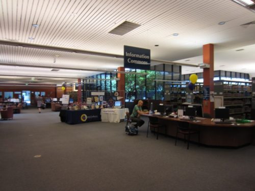 Information Commons Desk with directional sign above