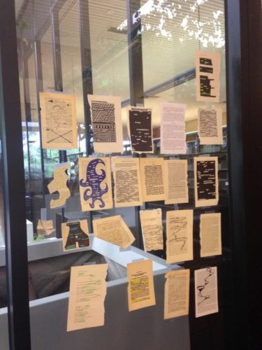 Students began to add their work to the atrium windows after writing poetry in a class session held in the atrium