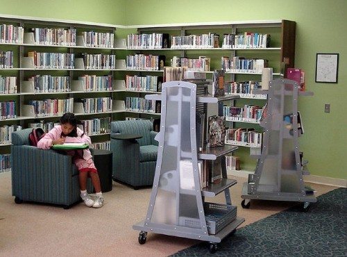 teen girl working at a chair in a public library