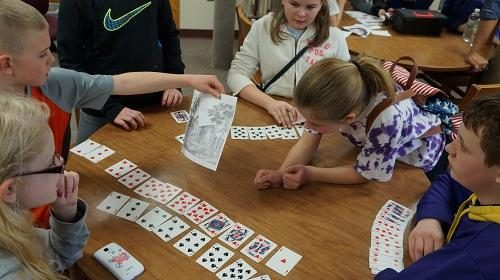 Children playing with cards to illustrate one of the puzzles in the lockdown room.